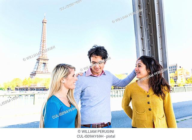 Friends near eiffel tower face to face smiling, Paris, France