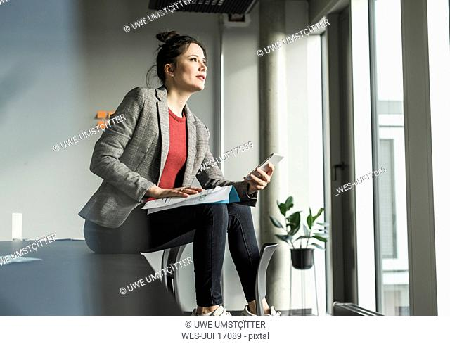 Businesswoman sitting on desk in office looking out of window