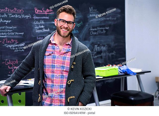 Young man in workplace wearing cardigan and glasses looking at camera smiling