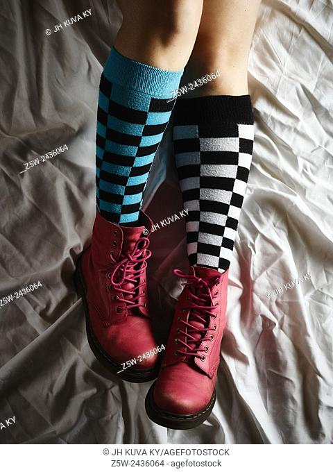 Girl lying on the bed and she wearing the socks and the pink shoes