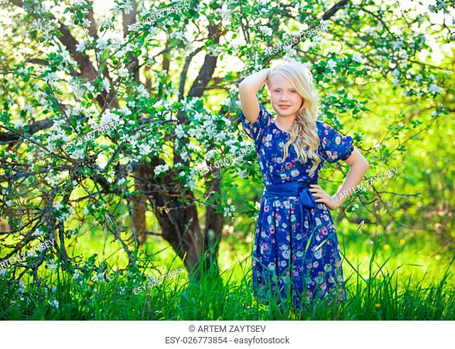 Adorable kid playing in nature. Cute little child, blonde toddler girl playing in blooming cherry garden on beautiful spring or summer day