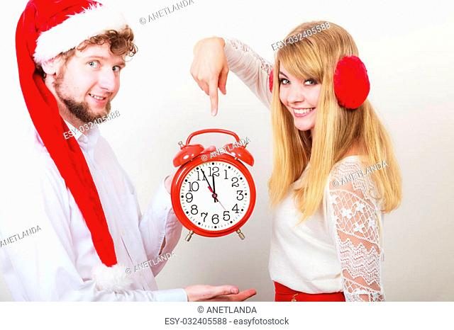 Happy cute couple holding alarm clock. Pretty woman in earmuffs and handsome man in santa claus hat on gray. Christmas time season concept