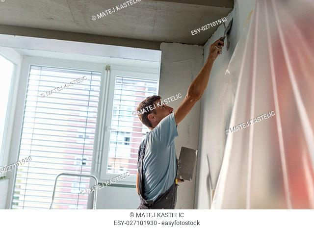 Thirty years old manual worker with wall plastering tools renovating house. Plasterer renovating indoor walls and ceilings with float and plaster