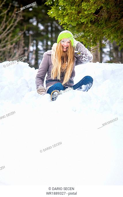 Woman Sitting In Snow, Spitzingsee, Bavaria, Germany