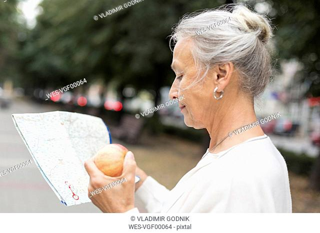 Senior woman outdoors holding map and apple