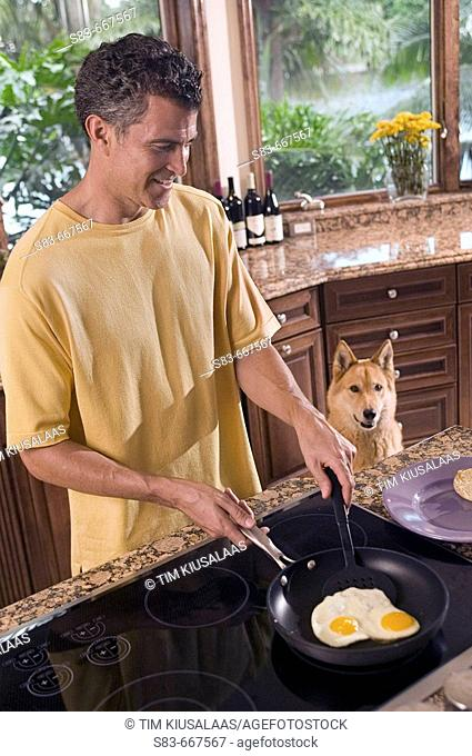 Man making eggs in kitchen with dog watching