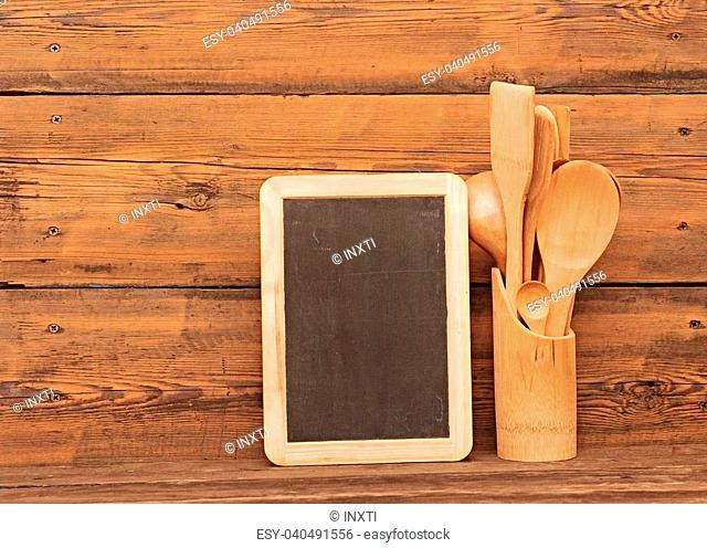 blank blackboard on wooden surface and wooden utensils