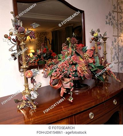 Still-Life of Autumn leaves and berries in floral arrangement on table with tall gilt candlesticks