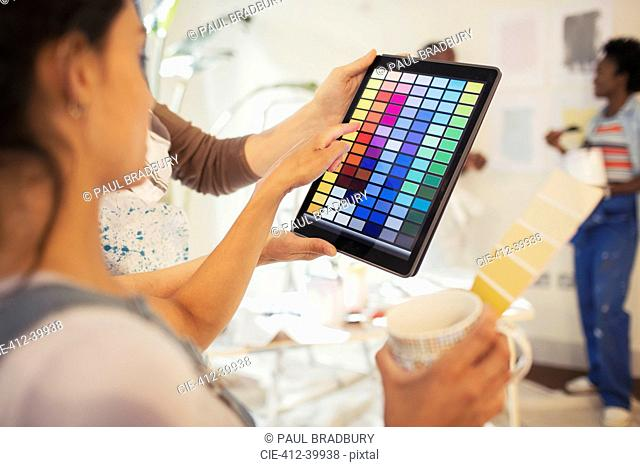 Young woman drinking coffee and viewing digital paint swatches on digital tablet