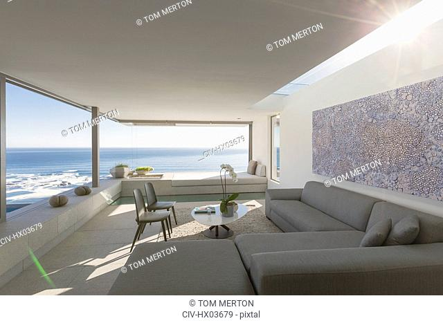 Sunny modern, luxury home showcase interior living room with ocean view