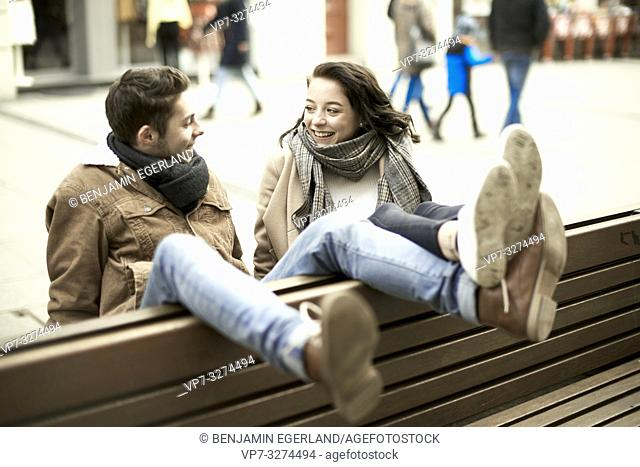 unconventional man and teenage woman sitting on bench the wrong way round, in city, legs up, upside down, in Cottbus, Brandenburg, Germany