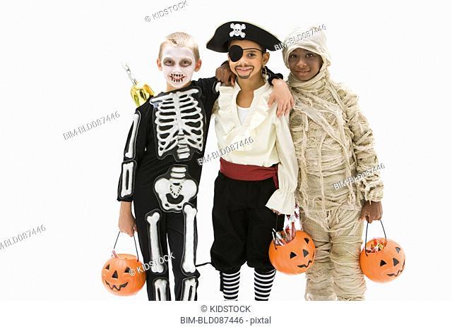 Boys in skeleton, pirate and mummy costumes holding jack o'lantern
