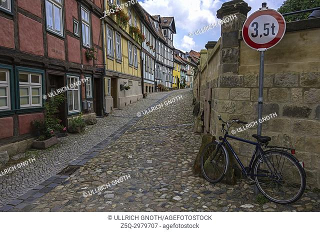 View through a narrow lane with historic listed half-timbered houses at Schlossberg in the Old Town of Quedlinburg, Saxony-Anhalt, Germany