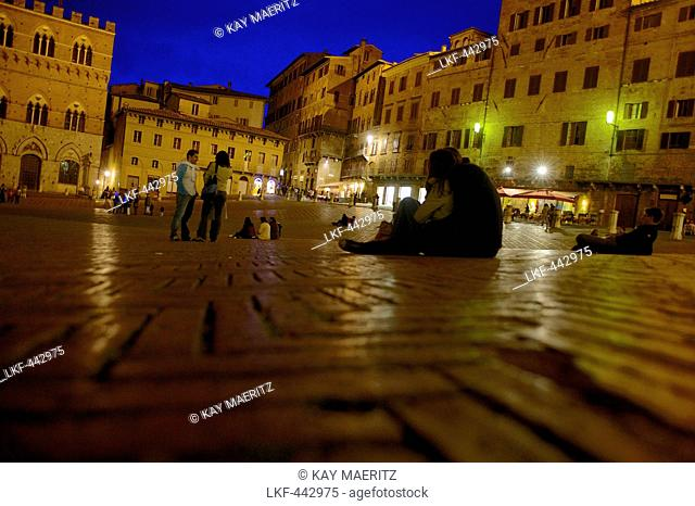 Visitors sitting on the cobbles of the Piazza del Campo at the Palazzo Pubblico, Siena, Tuscany, Italy