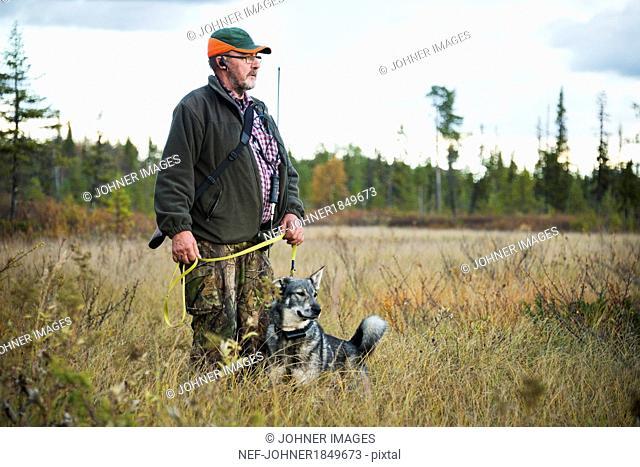 Senior man hunting with dog
