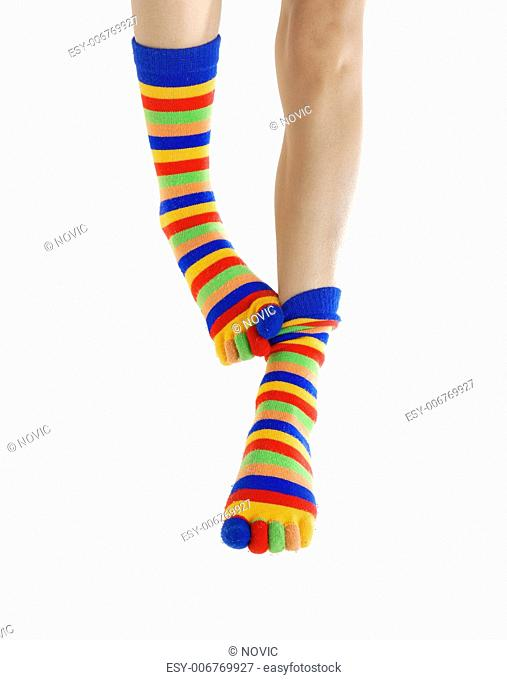 Thin legs in colored socks scratching each other