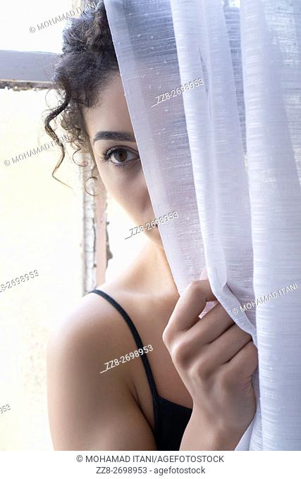 Woman hiding behind the blinds