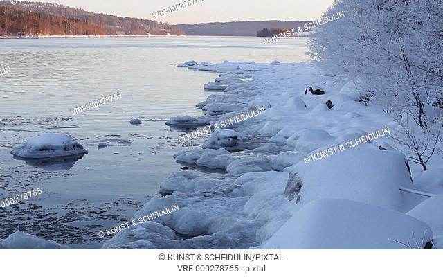 Waves rolling unto an ice-covered coast. Baltic Sea near Härnösand, Västernorrlands Län, Sweden