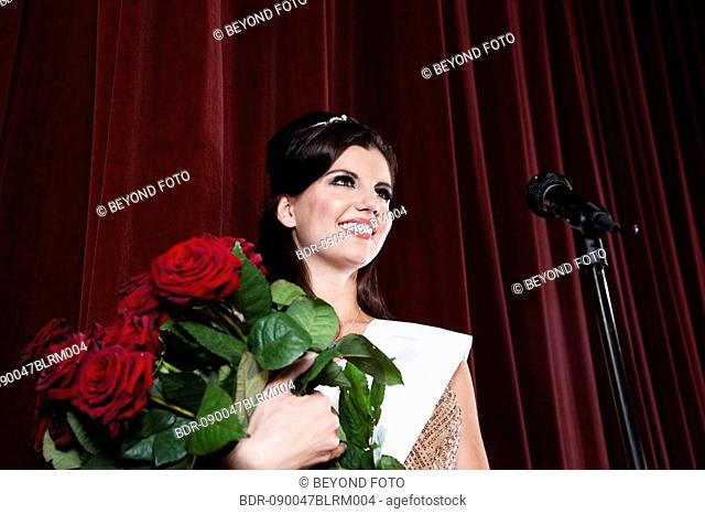 portrait of beauty queen with bunch of red roses on stage