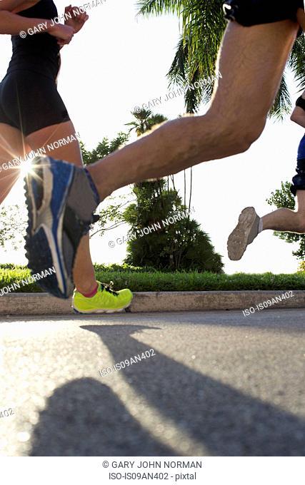 Legs of three mature adult runners on road run