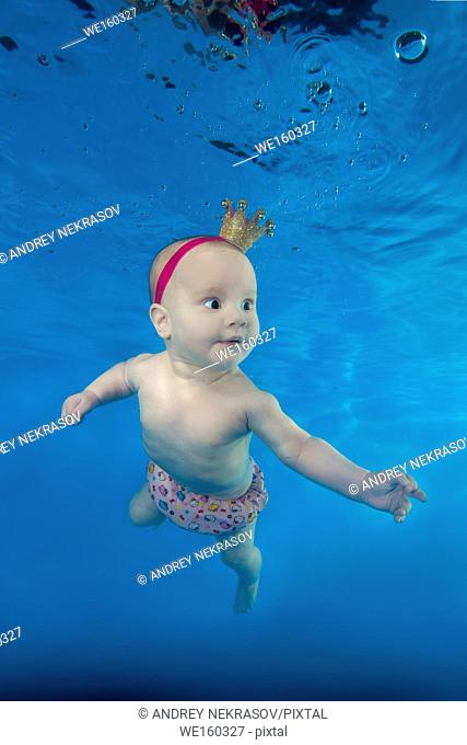 A little girl in a crown swims underwater in the pool
