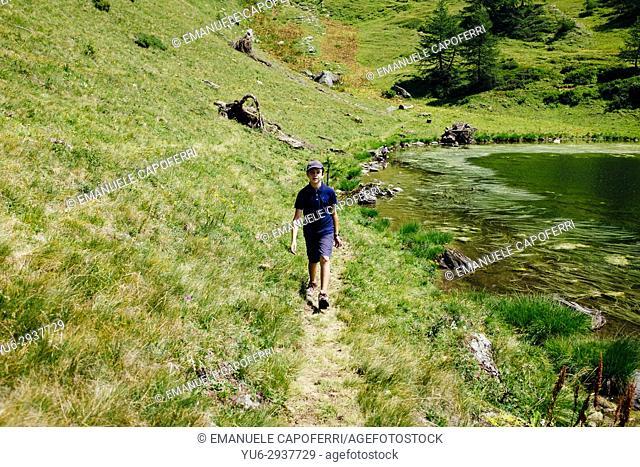little boy walking on mountain path. Alpe Devero, Piemonte, Italy