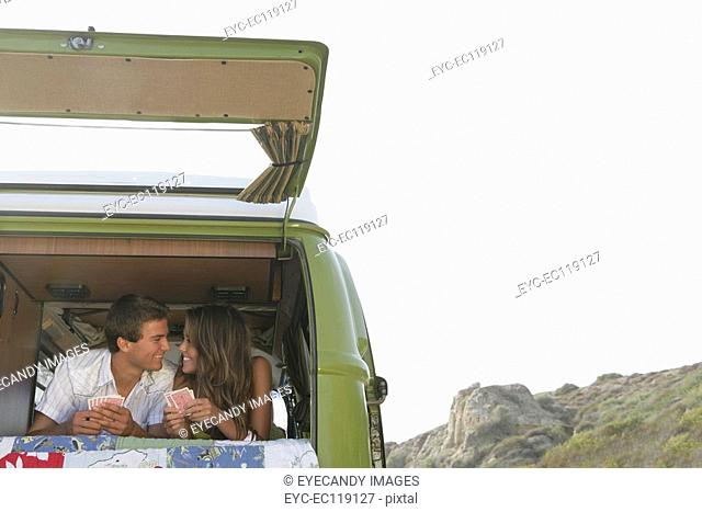 Couple playing cards in back of van