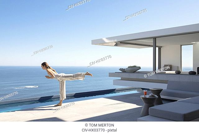 Woman practicing yoga warrior 3 pose on sunny modern, luxury home showcase exterior patio with ocean view