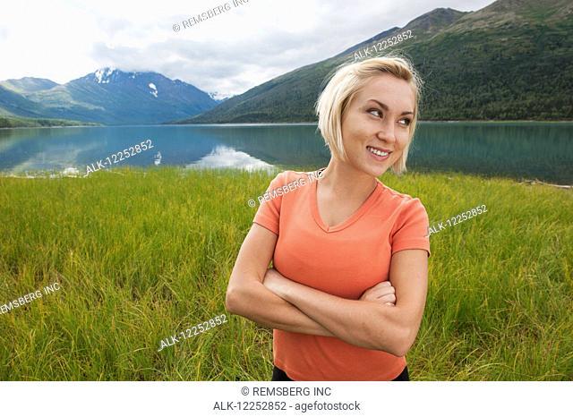 Female visitor standing among marsh grasses along Eklutna Lake, Chugach State Park, Southcentral Alaska