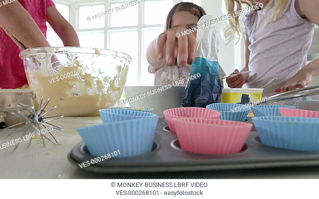 Three young girls spooning cake mixture into cases.Shot on Canon 5D Mk2 at a frame rate of 25fps