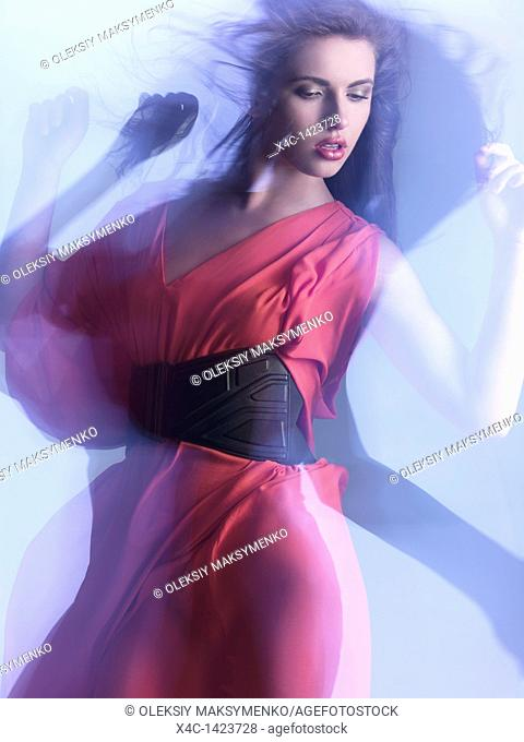 Futuristic dynamic high fashion photo of a young woman in a red dress posing in shiny neon light settings  The photo was not digitally manipulated
