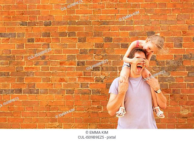 Girl getting shoulder carry from father with covering his eyes by brick wall