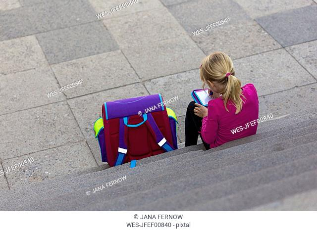 Back view of little girl with school bag sitting on stairs doing homework