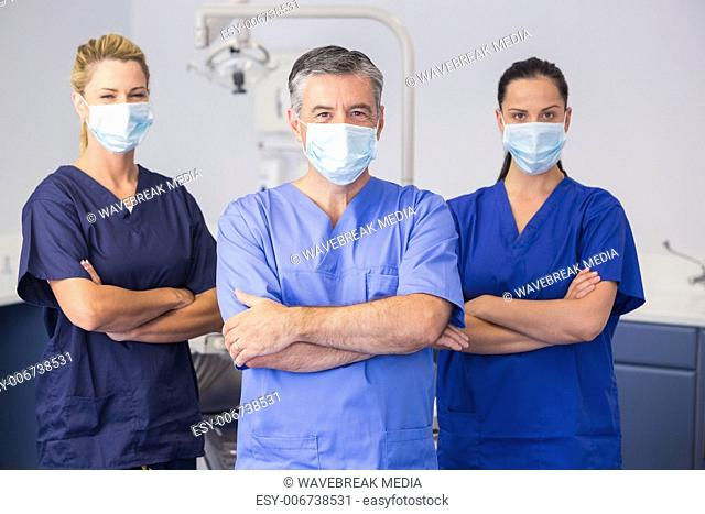 Co-workers wearing surgical mask with arms crossed