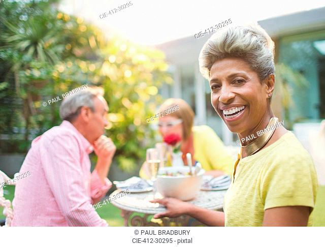 Portrait smiling mature woman enjoying lunch with friends in garden