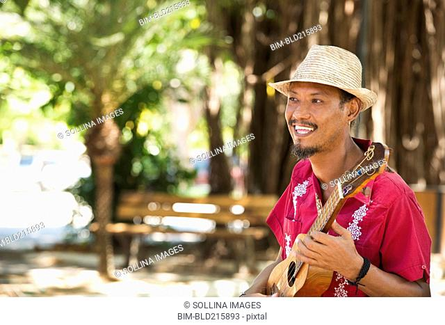 Hispanic musician playing ukulele in park