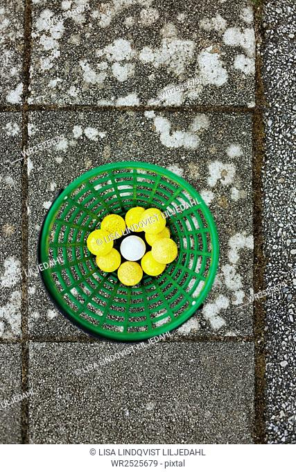 Directly above shot of golf balls in basket on paving stone
