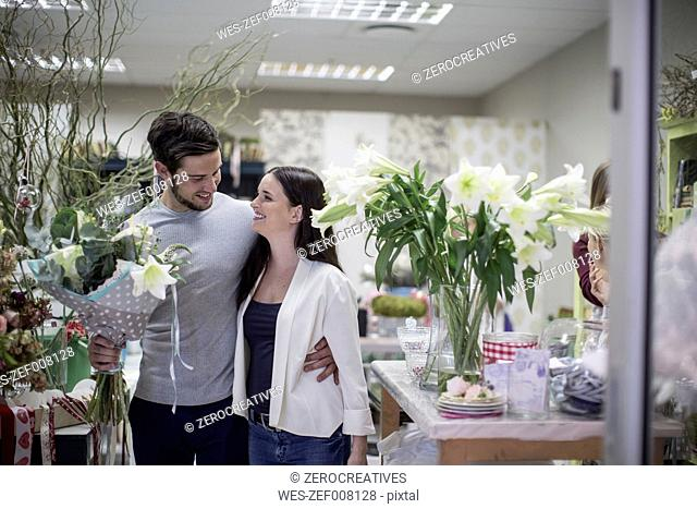 Happy young couple with bunch of flowers leaving flower shop