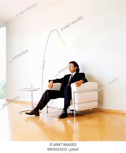 Businessman wearing dark suit sitting indoors on a leather armchair