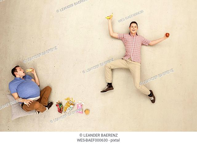 Men eating food against beige background
