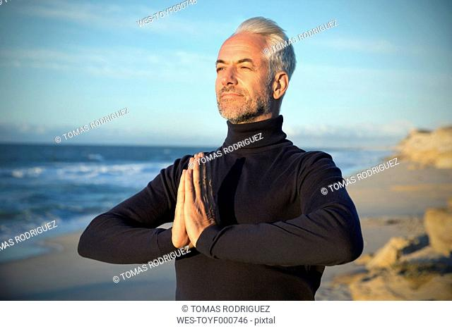 South Africa, portrait of man wearing turtleneck meditating on the beach before sunrise