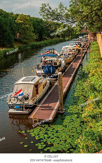 Trees, aquatic vegetation and boats anchored in pier on the bank of the river Dommel and blue sky in s-Hertogenbosch. Gracious historical city with vibrant...