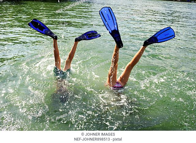 Two children bathing with diving flippers, Sweden