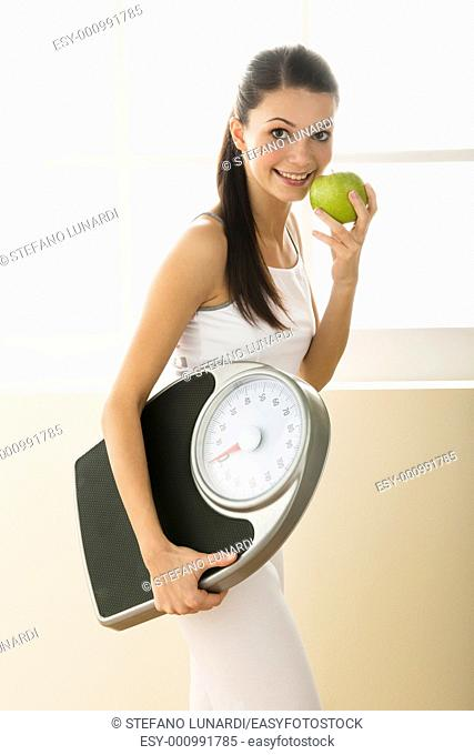 Young woman holding weight scale