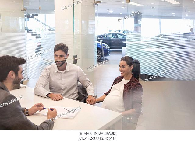 Car salesman talking to pregnant couple in car dealership office