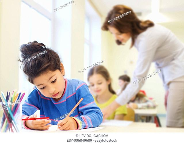 education, elementary school, children, creativity and people concept - happy little girl drawing with coloring pencils over classroom and teacher background