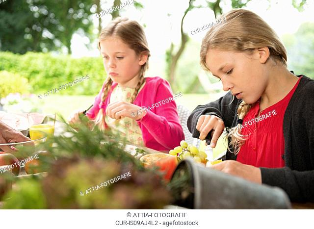 Two sisters at patio table slicing fresh fruit