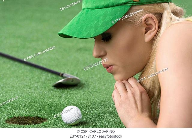 girl's playing with golf ball, she blows on that