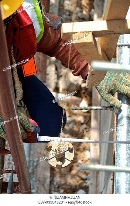Workers using measuring tape in their works at the construction site in Johor, Malaysia on November 14, 2015