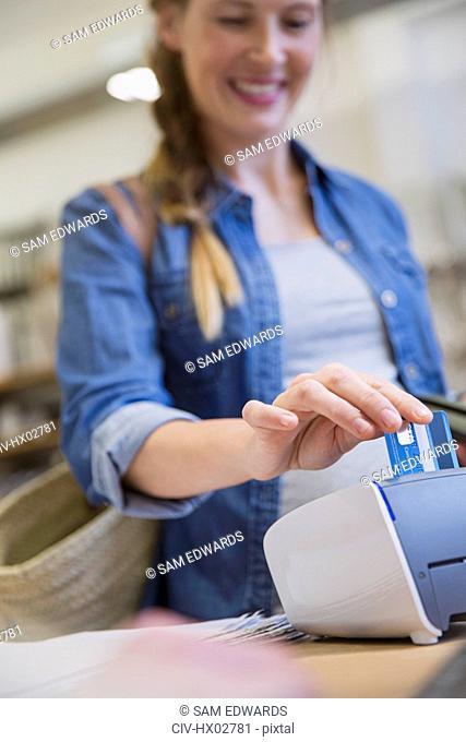 Female shopper using credit card reader in shop